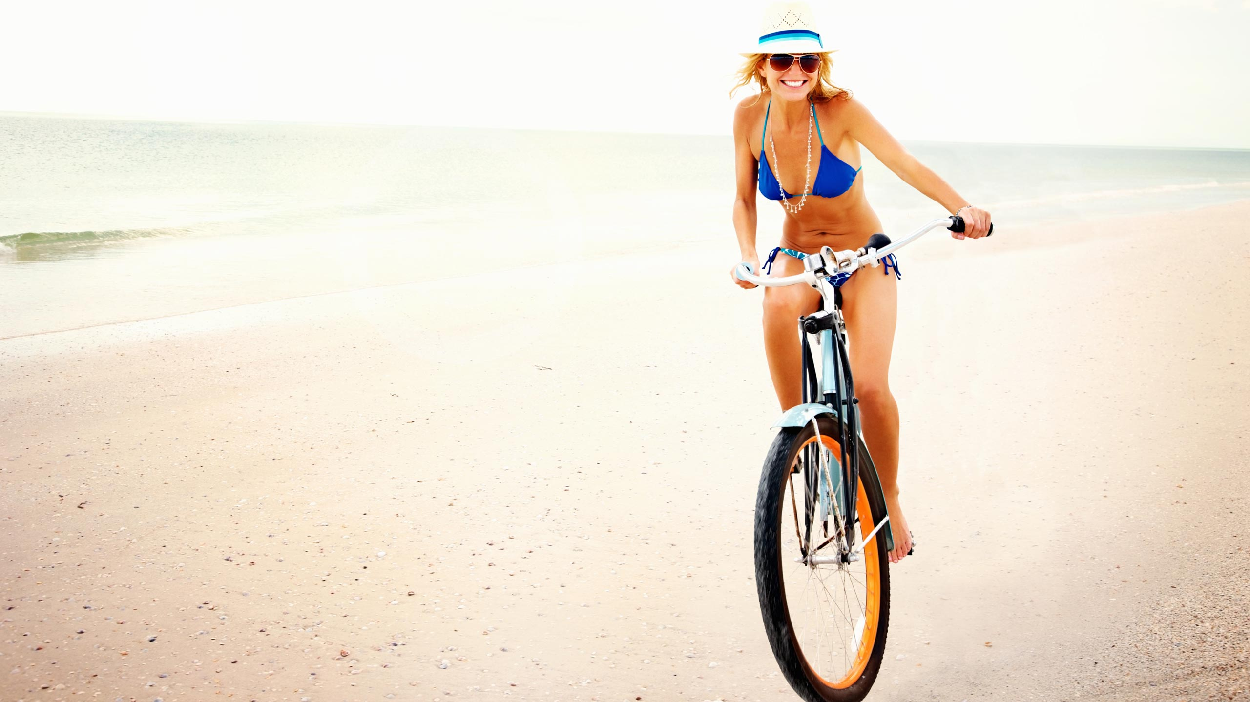 Girl cycling on the beach carefree