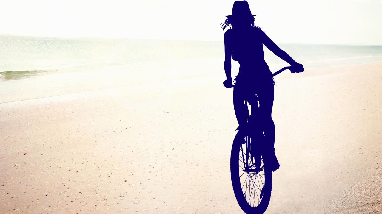 photoshop cut-out of girl cycling on the beach